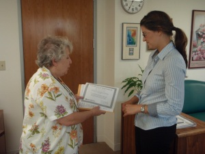 Mary delivers a certificate at Rep. Woolsey's office.