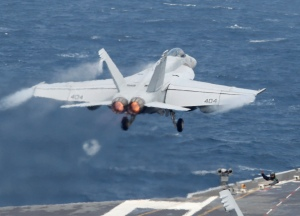 A crew member guides a U.S. Navy F/A-18 Super Hornet fighter taking off from the deck of U.S. aircraft carrier USS George Washington during joint military drills between the U.S. and South Korea in the West Sea